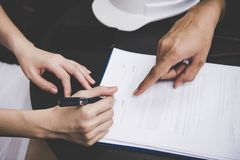 Woman hand signing a contract for building house with architect man. Stock Photo