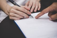 Woman hand signing a contract for building house with architect man. Contract Concept Stock Photos