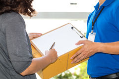 Woman hand signing receipt of delivered package. Delivery concep Stock Image