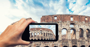 Woman hand with smartphone taking a picture of Colosseum in Rome Royalty Free Stock Photo