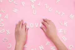Woman hand sorting letters LOVE on pink. Woman hand sorting letters LOVE on pink Royalty Free Stock Photo