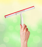 Woman hand with special squeegee for cleaning over bright Royalty Free Stock Images