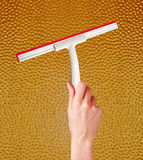 Woman hand with special squeegee for cleaning over glass Stock Photography