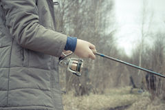 Woman hand with spinning and reel on the riverbank.  Stock Photography