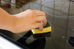 Woman hand with sponge cleaning ceramic hob Stock Photos