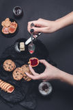 Woman hand with spoon  jam and biscuits near cup of coffee or cappuccino  chocolate cookies on black table background. Afternoon b Stock Photos