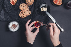 Woman hand with spoon  jam and biscuits near cup of coffee or cappuccino  chocolate cookies on black table background. Afternoon b Royalty Free Stock Photos