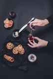 Woman hand with spoon  jam and biscuits near cup of coffee or cappuccino  chocolate cookies on black table background. Afternoon b Royalty Free Stock Photography