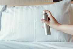 Woman Hand is Spraying Air Freshener into Pillow on Bedroom, Unpleasant Smell and Aromatherapy Concept.  royalty free stock photography