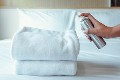 Woman Hand is Spraying Air Freshener to Towels in Bedroom, Unpleasant smell and Aromatherapy Concept stock images