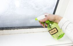 Woman hand spraying white vinegar solution natural cleaner on ugly unhealthy mold on home window.