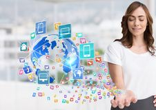 Woman with hand spread of with application icons coming up form it and earth Blurred office backgr Royalty Free Stock Photos