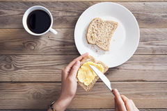 Woman hand spreading butter on sliced bread Stock Photography