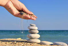 Woman hand sprinkles sand on pebble stack. On the beach Stock Photography