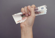 Woman hand squeezes russian money Stock Images