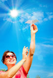 Woman hand starts paper plane in blue sky Stock Photography