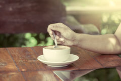 Woman hand stirred coffee in the cup in the coffee shop Stock Photos
