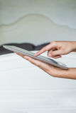 Woman hand on tablet pc, access for knowledge. Bedroom Royalty Free Stock Image