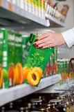 Woman hand take box of juice in grocery store Royalty Free Stock Photos