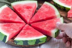 Woman hand take slice of fresh seedless watermelon cut into triangle shape laying on a wooden plate, horizontal. Woman hand take a slice of fresh seedless Royalty Free Stock Photo