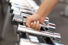 Woman hand takes dumbbell form rows of dumbbells in the gym royalty free stock photos