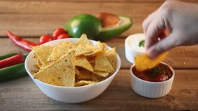 Woman hand takes Mexican chips nachos and dips in a sause salsa.  stock video footage