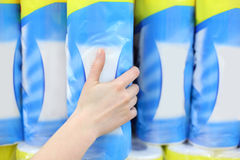 Woman hand takes pack of toilet paper in shop Stock Photo