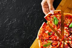 Woman Hand takes a piece of Pizza with Mozzarella cheese, Ham, Tomatoes, salami, pepper, pepperoni, Spices and Fresh Basil. Italia. N pizza on black background stock image