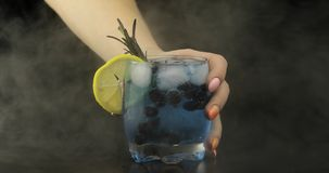 Woman hand takes refreshing soda lemonade blue cocktail royalty free stock image