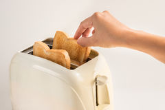 Woman hand taking bread out of toaster on white background Stock Photos