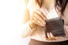 Woman hand taking money from black purse for payment. Woman spending money Royalty Free Stock Photography