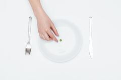 Woman hand taking one green pea from the plate Royalty Free Stock Photo