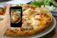 Woman hand taking a photo of Pizza with smartphone Stock Photo