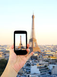 Woman hand taking pictures in front of Eiffel Tower, Cell phone Royalty Free Stock Images