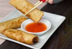 Woman hand taking spring roll with a chopstick Royalty Free Stock Images