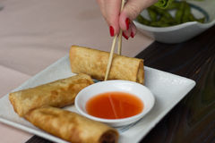 Woman hand taking spring roll with a chopstick. Edamame seen in the background Stock Photos