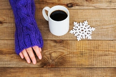 Woman hand in teal glove, mug with hot coffee or cocoa and snowf Stock Photos