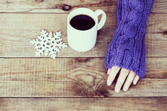 Woman hand in teal glove, mug with hot coffee or cocoa and snowf Stock Photography
