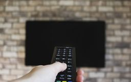 Woman hand with a television remote control and presses the button. royalty free stock image