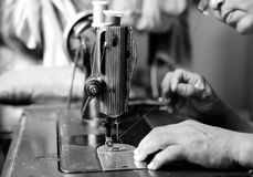 Woman hand threading needle into sewing machine needle Royalty Free Stock Images