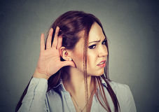 Woman with hand to ear gesture listening carefully royalty free stock photos