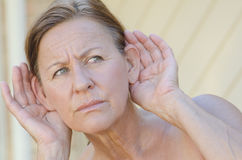 Woman hand to ear listening isolated outdoor III Stock Images