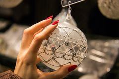 Woman hand touching Christmas ball beautiful ornamental decoration close up in white silver pearl colour, pretty fingers with red stock photo