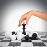 Woman hand touching king figure on chess board Stock Images