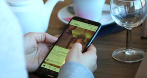 Woman Hand Touching Smartphone With Instagram App In A Restaurant