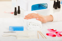 Woman hand on towel, next to manicure set Royalty Free Stock Photography