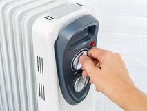 Free Woman Hand Turns On The Thermostat Knob Of An Electric Oil Heater. White Oil-filled Radiator For Home And Office. House Heating Royalty Free Stock Photos - 163209058
