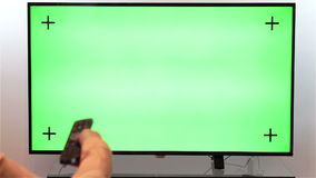 Woman hand with TV remote switching channels on a green screen TV stock video footage