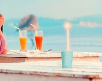 Woman hand , two glasses with fresh fruit juices, burning candle on wooden table in cafe on the beach. stock images