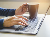 Woman hand type on Laptop Keyboard with Coffee cup. Morning light Stock Images
